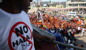 A supporter of nationalist Buddhist monks wears a T-shirt calling for a ban on Islamic halal-slaughtered meat, during a rally at Maharagama, a suburb of the capital Colombo, February 17, 2013. A new group known as the Bodu Bala Sena, or Buddhist Force, launched a drive to press for a boycott of all halal products in a country where the majority are Buddhists. AFP PHOTO/Ishara S.KODIKARA